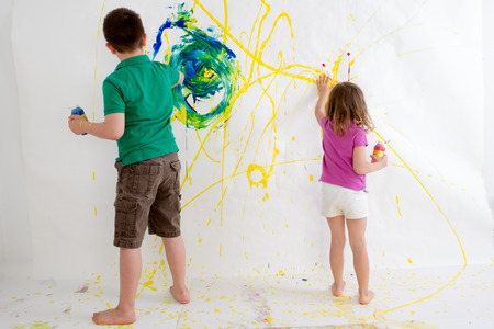 Two young children, a ten year old boy and three year old girl, freehand painting on a wall with colorful acrylic paints creating an abstract design viewed from behind