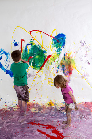 Young brother and sister painting together creating a modern abstract of vivid colors on the wall and floor using their imagination and creativity