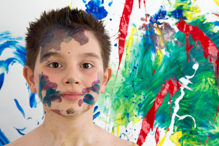 daubed: Handsome young boy daubed with colorful paint all over his face standing in front of his new modern abstract artwork with a blend of vibrant colors