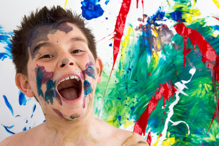 daubed: Funny artistic little boy with paint splodges on his face standing in front of his completed modern abstract creation laughing at the camera with his mouth wide open Stock Photo