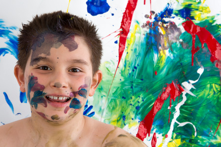 daubed: Happy creative little boy with paint splodges on his face standing in front of his bright colorful modern abstract painting grinning at the camera Stock Photo