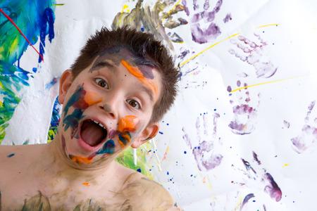 niño sin camisa: Emocionado niño feliz haciendo pintura de dedo de pie riendo a la cámara con una boca abierta delante de su obra con colores vibrantes y huellas de las manos