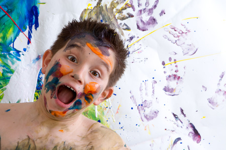 Excited happy little boy doing finger painting standing laughing at the camera with a wide open mouth in front of his artwork with vibrant colors and hand prints