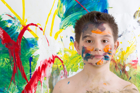 daubed: Young artist posing shirtless with his face covered in paint splodges with his modern art of colorful blended abstract patterns looking at the camera