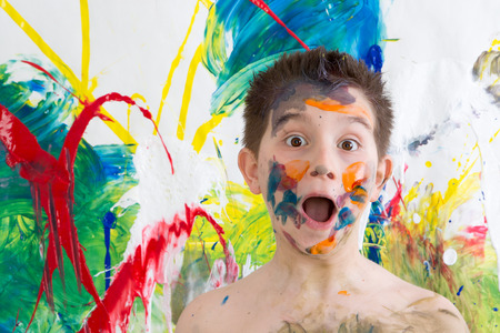 daubed: Astonished little boy with his face covered in colorful paint splodges gawping at the camera in front of a modern abstract painting in vibrant colors