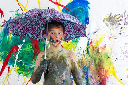 asombro: Niño pequeño lindo sin camisa divertida cubierto de pintura fresca de pie bajo un paraguas frente a su vibrante arte contemporáneo colorido mirando a la cámara con una mirada asombrada