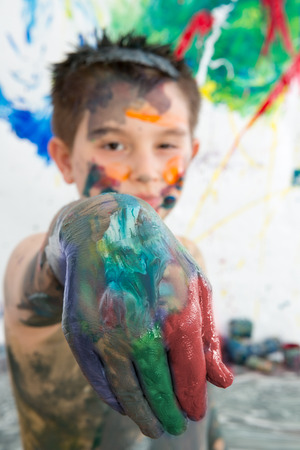 daubed: Artistic little boy holding out his paint covered hand to the camera as he stands in front of his modern abstract painting