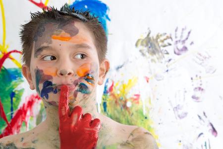 Muchacho pensativo poco creativo cubiertos de pintura de pie con el dedo a los labios mirando contemplativamente a un lado frente a su obra de arte contemporánea en su búsqueda de la inspiración Foto de archivo - 39534630