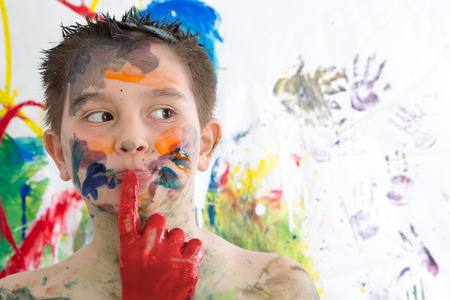Thoughtful creative little boy covered in paint standing with his finger to his lips looking contemplatively to the side in front of his contemporary artwork as he seeks inspiration Stock Photo