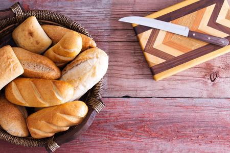 marqueteria: Surtido de pan fresco en una cesta listo para ser servido para la cena de pie sobre una mesa de madera r�stica junto a una tabla para cortar madera con incrustaciones decorativas y cuchillo, de arriba con copyspace Foto de archivo