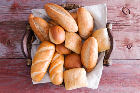 accompaniment: Assorted crusty fresh golden bread rolls in a basket in different speciality shapes displayed on a rustic wooden buffet table as an accompaniment to a meal