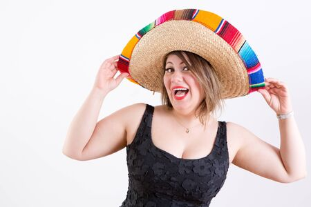 Close up Smiling Lady in Sleeveless Black Shirt with Mexican Sombrero on her Head, Looking at Camera, Emphasizing Welcome to the Party Gesture. Captured Indoor with White .