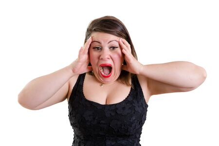 Terrified woman wearing low-cut sleeveless black top while holding her head with both hands as a gesture of panic and shock, isolated portrait with copy space on white