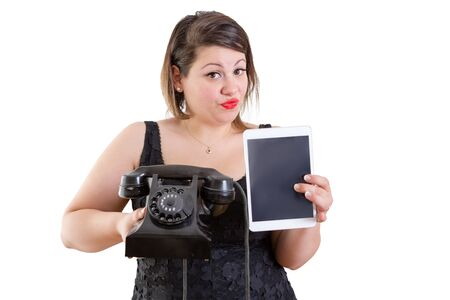 quizzical: Charismatic woman comparing old and modern technology holding up an old-fashioned rotary land line telephone instrument and a tablet computer in a communications concept, isolated on white Stock Photo