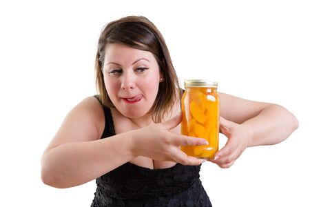 Plump woman licking her lips in anticipation as she eyes a jar of appetizing tempting homemade peaches she is holding in her hand in a health, nutrition and diet concept, isolated on white