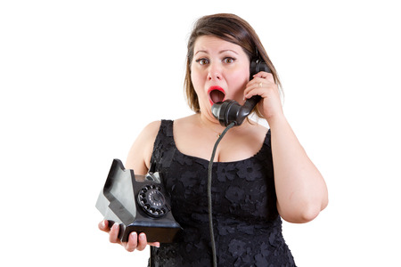reacting: Astonished woman talking on an old fashioned rotary telephone reacting to surprising news in a communications concept on white
