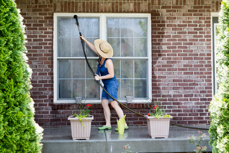 Housewife standing on a patio washing the windows of her house with a hose attachment as she spring-cleans the exterior at the start of the new spring season Archivio Fotografico