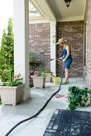 hosepipe: Woman gardener standing watering newly potted decorative spring plants arranged in flowerpots along an open-air patio using a hosepipe and sprinkler spray