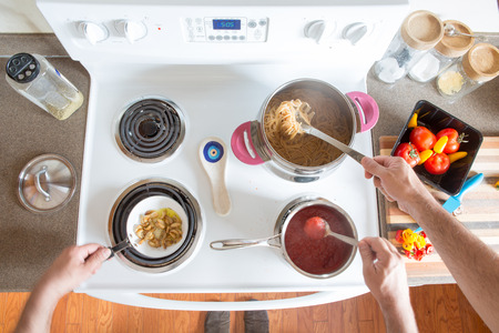 boiling: Two men preparing healthy brown wholewheat spaghetti cooking together at the hob as a team stirring the boiling pasta and sauce, overhead view of their hands and ingredients Stock Photo