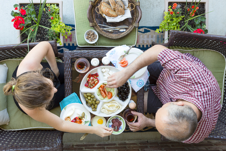 haloumi: Man and woman enjoying an outdoor Turkish breakfast sitting together at a small intimate table helping themselves to a selection of food with Turkish tea, overhead view Stock Photo