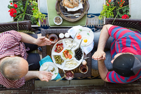 denominational: Two multi denominational men praying over food as they prepare to enjoy a healthy Mediterranean breakfast wit Turkish tea, overhead view on an outdoor patio Stock Photo