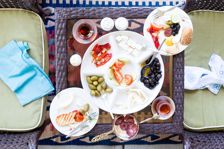 haloumi: Unfinished Turkish breakfast on a patio table with a serving of fried eggs with a selection of fresh tomato, olives, cheese and mugs of Turkish tea, overhead view with napkins on chairs Stock Photo