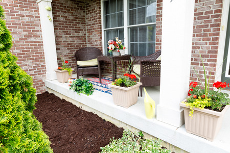 patio chairs: Mulching flowerbeds around the house with a freshly mulched bed alongside an open-air patio decorated with ornamental flowers Stock Photo