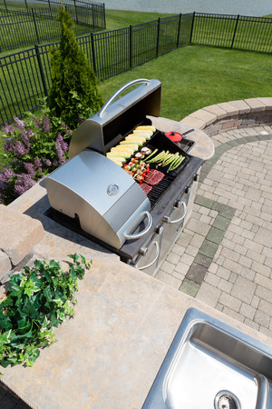 Healthy outdoor living cooking in a summer kitchen fitted with a sink and counter and large gas barbecue loaded with fresh vegetables and meat on an open-air brick patio in the back garden Stockfoto