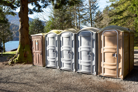 Portapotty, or portable enclosed plastic portable toilet with chemicals and deodorizers in a tank, in a park yard for public convenience 写真素材