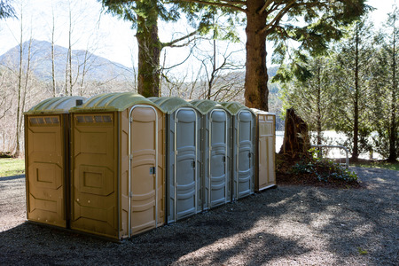 Row of public Portapotty toilets in a park for public ablutions using chemical toilets and deodorizers for smell, standing in the shade of a tree with closed doors