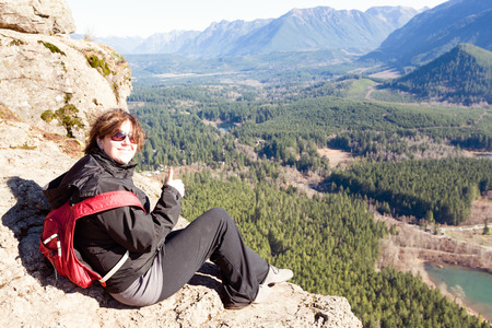 ledge: Smiling happy woman wearing a backpack on the Rattlesnake Ledge Trail, Snoqualmie, Washington, sitting on a rocky ledge enjoying the view of the lake, valley and mountains below Stock Photo