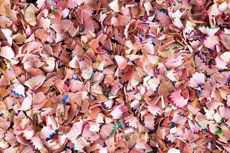 sharpening: Background texture of colorful wood shavings left behind when sharpening colored pencils crayons for art or school in a random full frame multicolored scatter