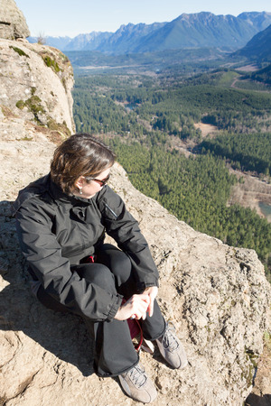ledge: Young woman wearing sunglasses sitting on a rocky outcrop enjoying the view of the forested valley, lake and mountains from Rattlesnake Ledge Trail, Snoqualmie, Washington after hiking up the summit Stock Photo
