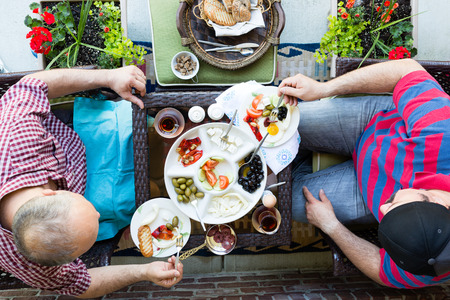 neighbour: Two men having a discussion over a healthy fresh Turkish style breakfast as they sit outdoors at a table on a patio together, overhead view