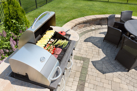 outdoor living: Grilling healthy food with corn, kebabs, meat and sausages on an outdoor gas barbecue on a luxury brick paved patio and summer kitchen in a neatly manicured back yard