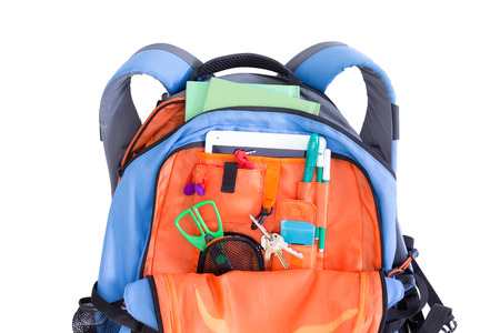 Orange and blue kids school backpack packed with a tablet, notebooks, scissors, pens, books, and stationery ready for a creative art class in an educational concept, on white
