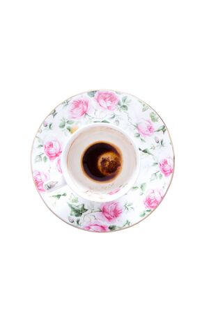 centred: Finished cup of Turkish in a dainty pretty floral porcelain cup and saucer decorated with pink roses coffee viewed from above isolated on white Stock Photo