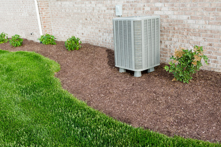 install: Air conditioner condenser unit standing outdoors in a garden in a neat clean mulched flowerbed for easy access for maintenance Stock Photo
