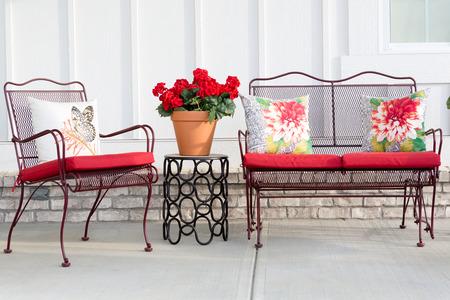 jardines con flores: Colorido muebles de jard�n de hierro forjado con cojines rojos vibrantes y un geranio en maceta roja que se coloca en un patio frente al aire libre o porche listo para la primavera y el verano el clima c�lido