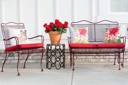 Colorful wrought iron garden furniture with vibrant red cushions and a red potted geranium standing on an open-air front patio or porch ready for the warm spring and summer weather