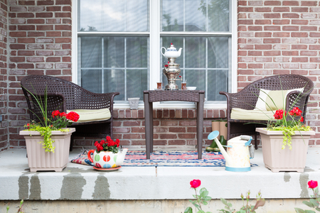Wicker furniture on the patio with a samovar and tea cups ready for a relaxing tea break in the spring sunshine with pretty flowering potted plants