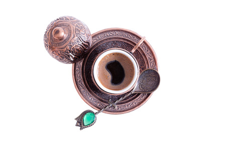addictive drinking: Cup of freshly brewed hot frothy Turkish coffee served in a traditional cup with lid with a decorative teaspoon, overhead view isolated on white