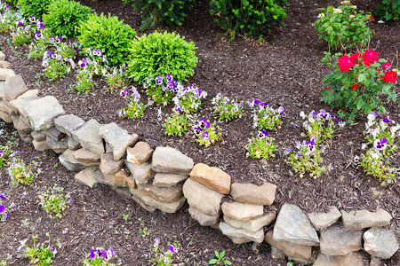 garden landscaping: Natural rock retaining wall in a garden with rough rocks and stones arranged in a curve for a formal raised bed of flowering plants in a garden landscaping concept