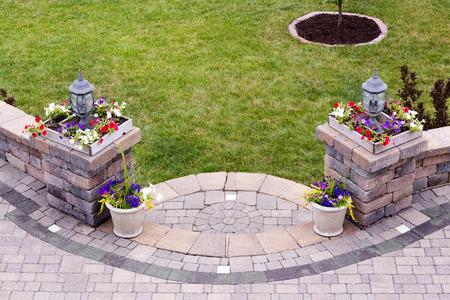 Gebogen ingang van een buiten patio met ondiepe stappen die leiden tot een baksteen geplaveid woonkamer geflankeerd door twee zuilen met lampen en kleurrijke bloemen in vierkante potten, hoge hoek bekijken met groene gras
