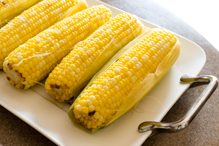 mealie: Row of delicious boiled fresh corn cobs for a healthy snack served with butter on a platter, close up view Stock Photo
