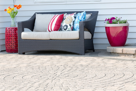 settee: Comfortable modern deep seating settee on an outdoor brick paved patio with a circular pattern decorated with red ceramic flowerpot and pedestal table with colorful flowers