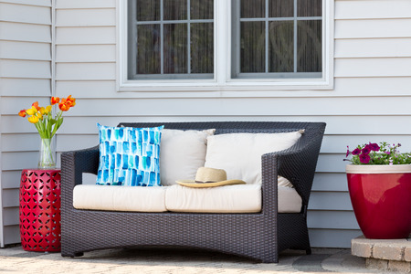 Comfortable outdoor living area on a brick patio with a deep seating settee and cushions flanked by red ceramic pedestal table and flowerpot with spring flowers and a straw sunhat Banque d'images