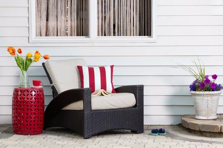 リラックスしてティータイム休憩カラフルな春の花の季節の日差しを楽しんでいる快適な深い座席肘掛け椅子で屋外のパティオで 写真素材