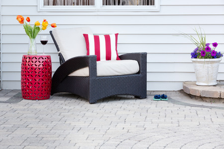 Single armchair with a red ceramic pedestal table and vase of spring tulips with a matching striped red and white cushion on a brick paved outdoor patio for a relaxing break