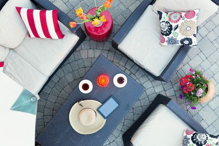Relaxing on a brick patio by candlelight in the evening with two cups of tea and a straw sunhat on a table surrounded by deep seating comfortable armchairs and flowers, overhead view
